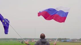 人挥动欧盟和俄罗斯的旗子在国家风景 友谊的概念和 影视素材
