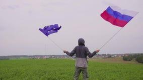 人挥动欧盟和俄罗斯的旗子在国家风景 友谊的概念和 股票录像