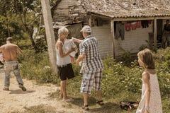 人捐赠一块布料和其他不同的事给当地古巴村庄人民 库存照片
