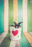 仙人掌在减速火箭的葡萄酒背景的心脏花瓶开花 免版税库存图片