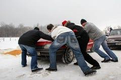 人推挤在被冰的路阻拦的汽车 库存照片