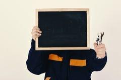 人掩藏在空的黑板后的面孔在白色背景 水管工用金属扳手设备在手中 免版税库存照片