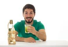 年轻人提出与基于柠檬的鸡尾酒和cachaca的一块玻璃 免版税库存照片