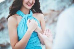 人提出结婚提议给他的女朋友,结婚提议agains山,妇女愉快由于 库存照片