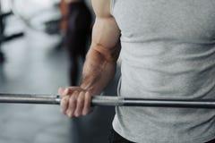 人提取dumbell的关闭在健身房 锻炼与制定出健康的节目 免版税库存图片