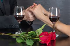 人握女孩的手的在餐馆桌上的与两个红酒酒杯和英国兰开斯特家族族徽开花 免版税库存照片