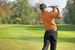 年轻人摇摆的高尔夫俱乐部,背面图 库存图片