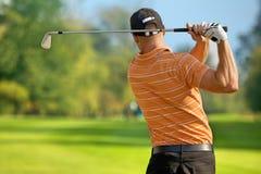 年轻人摇摆的高尔夫俱乐部,背面图 图库摄影