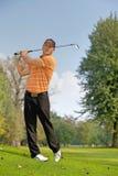 年轻人摇摆的高尔夫俱乐部 库存照片