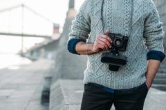 人播种的射击时髦的毛线衣的有葡萄酒影片照相机的户外 免版税图库摄影