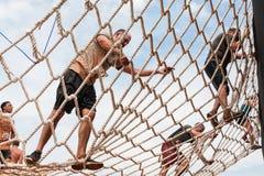 人攀登在极端障碍桩种族的吊货网 库存照片
