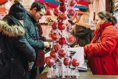 人支付甜点在冬天妙境圣诞节市场的一个摊位在伦敦,英国 免版税库存图片