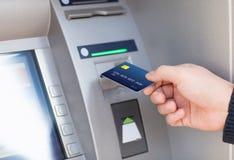 人放信用卡入ATM 库存照片
