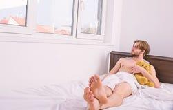 人放置有玩具的白色床单 人不剃须的有胡子的面孔放松与喜爱的玩具熊 人帅哥放松 免版税库存图片