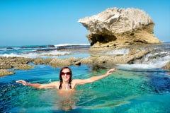 令人敬畏的多岩石的海滩的愉快的少妇 图库摄影