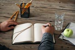 人文字的手某事在空白的笔记本 免版税库存图片