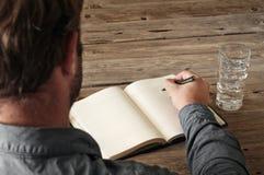 人文字的手某事在空白的笔记本 免版税库存照片