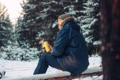 人旅客林务员猎人在冬天森林里坐下落的树 库存照片