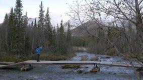 人旅客横渡在桥梁的一条山小河 美丽的景色 影视素材