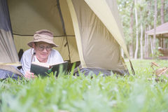 年轻人旅游在和在帐篷的阅读书在露营地 库存照片