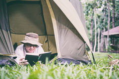 年轻人旅游在和在帐篷的阅读书在露营地 库存图片