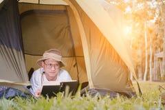 年轻人旅游在和在帐篷的阅读书在露营地 免版税图库摄影