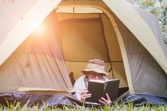 年轻人旅游在和在帐篷的阅读书在露营地 免版税库存照片
