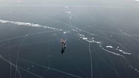 人旅游步行去光滑的表面上 美丽如画的贝加尔湖崩裂蓝色光滑的清楚的冰小丘下雪随风飘飞的雪 股票录像