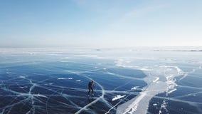 人旅游步行去光滑的表面上 美丽如画的贝加尔湖崩裂蓝色光滑的清楚的冰小丘下雪随风飘飞的雪 股票视频