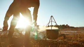 人旅游远足者是坐由篝火在自然野营的剪影阳光日落的止步不前党的啤酒 人剪影 股票录像