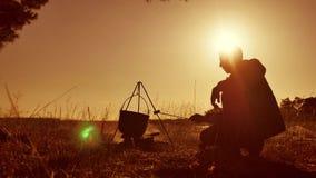 人旅游远足者生活方式是坐由篝火在自然野营的剪影阳光日落的止步不前党的啤酒 人 股票录像