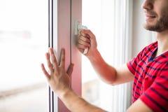 人早晨在家打开窗口刷新屋子 免版税库存照片