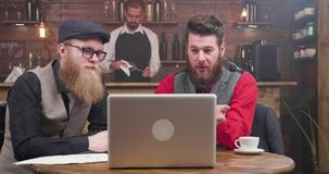 人时髦的衣服的和有好的胡子的有电视电话会议在一个不拘形式的环境 股票录像