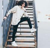年轻人时兴地打扮了摆在金属楼梯的凉快的成套装备的人 蓬松卷发样式头发 Streetstyle 青年时尚 库存照片