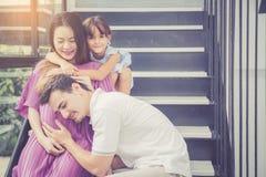 人是听怀孕妻子,亚裔英俊的父亲小心母亲和孩子与夫妇并且预计母道有一愉快 库存照片