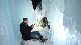 人是坐片剂的互联网在冰洞 在神奇美丽的冰洞穴附近 用户沟通  影视素材