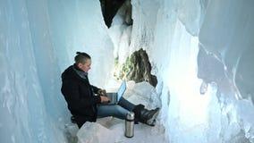 人是坐膝上型计算机的互联网在冰洞 在神奇美丽的冰洞穴附近 用户沟通  免版税库存照片
