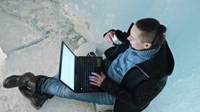 人是坐膝上型计算机的互联网在冰洞 在神奇美丽的冰洞穴附近 用户沟通  股票视频