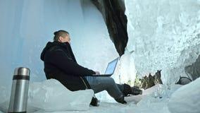 人是坐膝上型计算机的互联网在冰洞 在神奇美丽的冰洞穴附近 用户沟通  股票录像