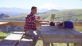 人是工作在膝上型计算机和喝从在山背景的一个杯子的自由职业者  股票视频