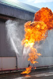 人是的小组消防队员注射浪花水射击acc 图库摄影