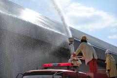 人是的小组消防队员注射浪花水射击acc 免版税图库摄影