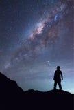 人是站立和看见在夜空的银河星系 库存照片
