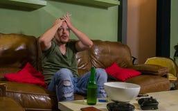 人是被惊吓和吃在电视前面的玉米花 免版税图库摄影