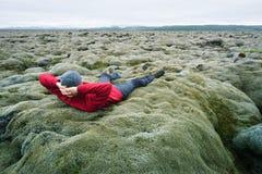 人是青苔的一个旅客在一个熔岩荒野在冰岛 免版税图库摄影
