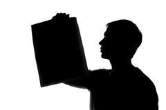 年轻人显示一张报纸,纸片-剪影 免版税图库摄影