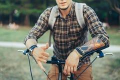 年轻人显示吊宽松Shaka冲浪者标志用手坐在绿色夏天草甸的一辆自行车 免版税库存图片