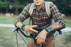 年轻人显示和平或胜利的迹象坐在绿色夏天草甸的一辆自行车 免版税图库摄影