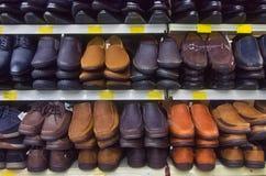 人显示的品种鞋子在架子在商店 免版税库存照片