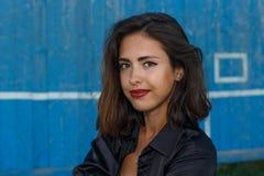 年轻人晒黑了一件短的上面和衬衣的摆在对蓝色木墙壁的妇女有美好的现代构成的和头发 库存照片